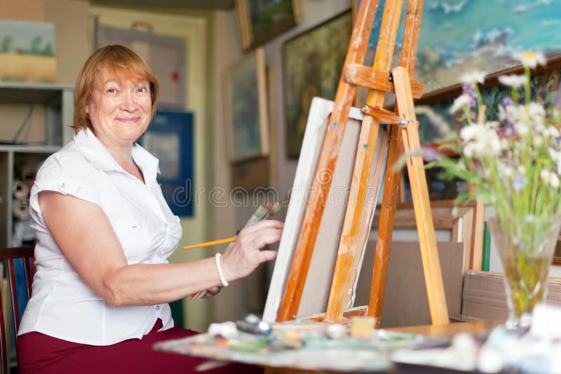Женский художник красит что-нибыдь на холстине стоковое изображение