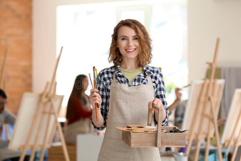 Женский художник с инструментами и красками в мастерской стоковое фото rf