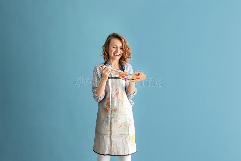 Женский художник с палитрой щетки и краски на предпосылке цвета стоковое изображение