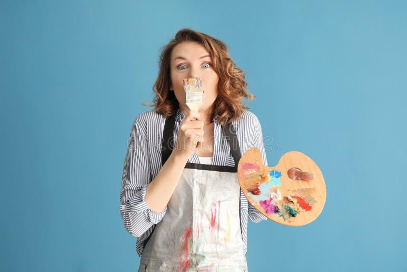 Женский художник с палитрой щетки и краски на предпосылке цвета стоковые изображения