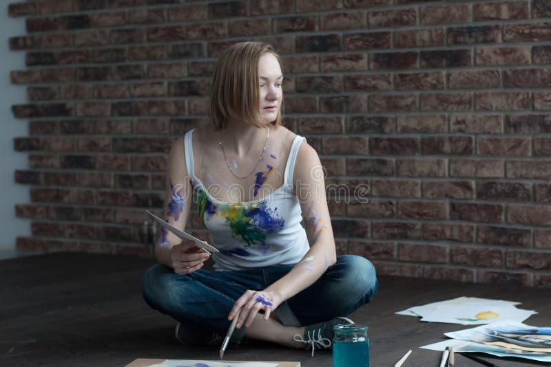 Женский художник рисует в комнате стоковая фотография