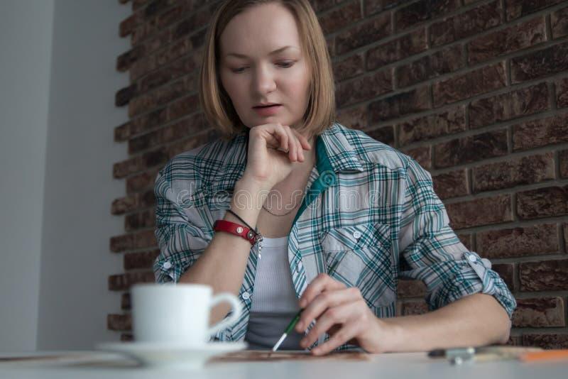 Женский художник рисует в комнате стоковые изображения