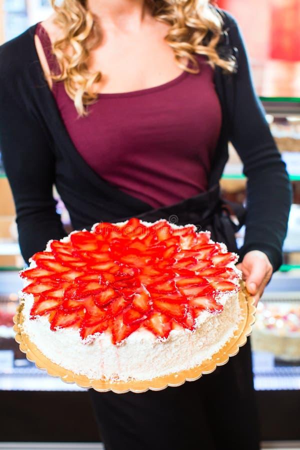 Download Женский хлебопек представляя торт в кондитерскае Стоковое Фото - изображение насчитывающей confectioner, десерт: 40585992