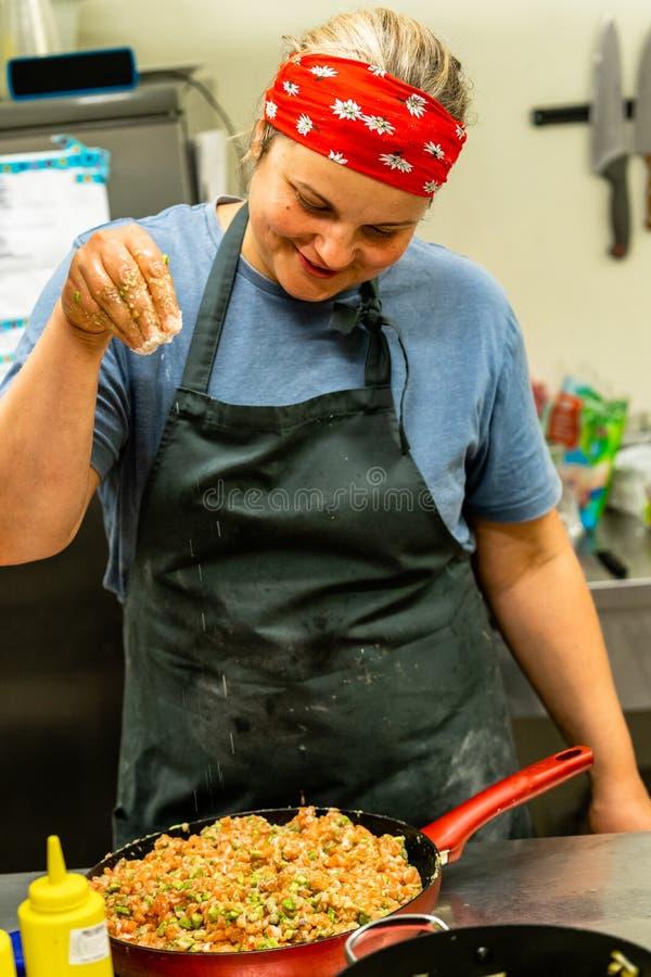 Женский шеф-повар добавляя соль к смешиванию семг и авокадоа в красном лотке стоковое фото