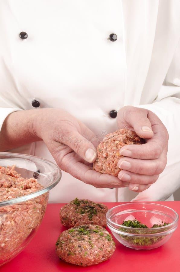 Женский шеф-повар подготовляя шарики мяса стоковые изображения