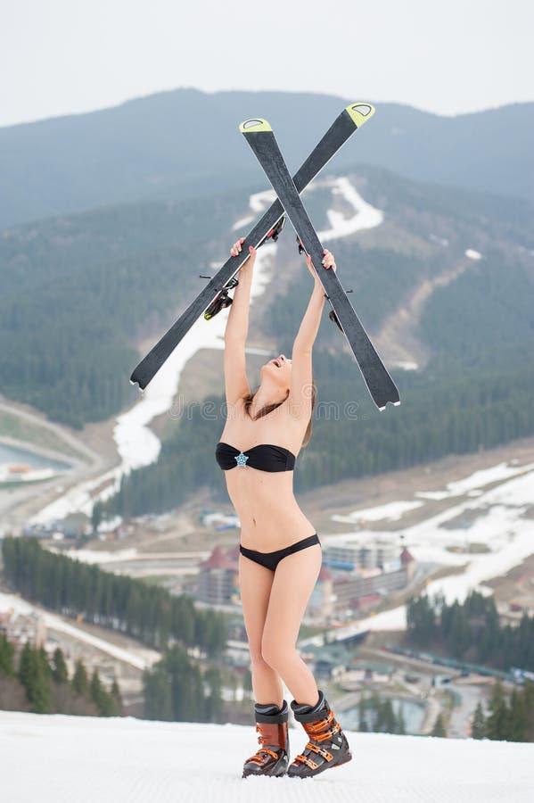 Женский лыжник стоя на верхней части наклона и держа лыжи над головой Нося купальник, ботинки лыжа курорта стоковая фотография rf