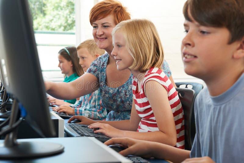 Женский элементарный зрачок в классе компьютера с учителем стоковая фотография rf