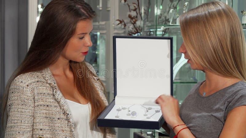 Женский ювелир показывая красивый набор в коробке к ее клиенту стоковое фото