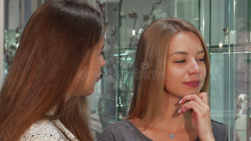 Женский ювелир помогая ее женскому клиенту выбирая ювелирные изделия для покупки стоковое фото rf