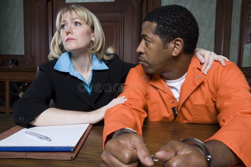 Женский юрист с преступником в зале судебных заседаний стоковые фото