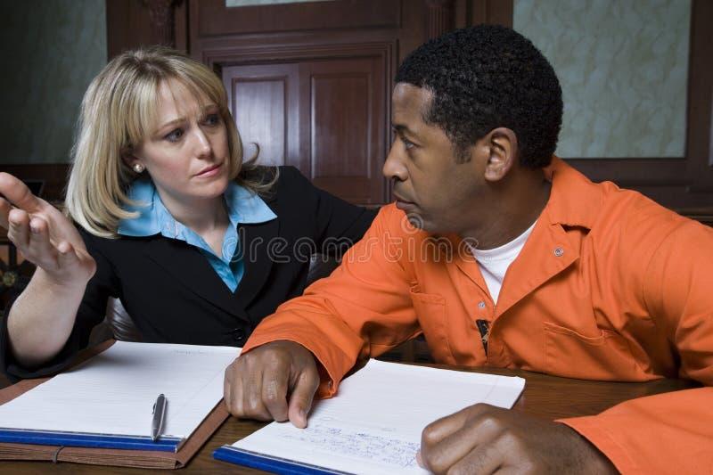 Женский юрист с преступником в зале судебных заседаний стоковые изображения rf