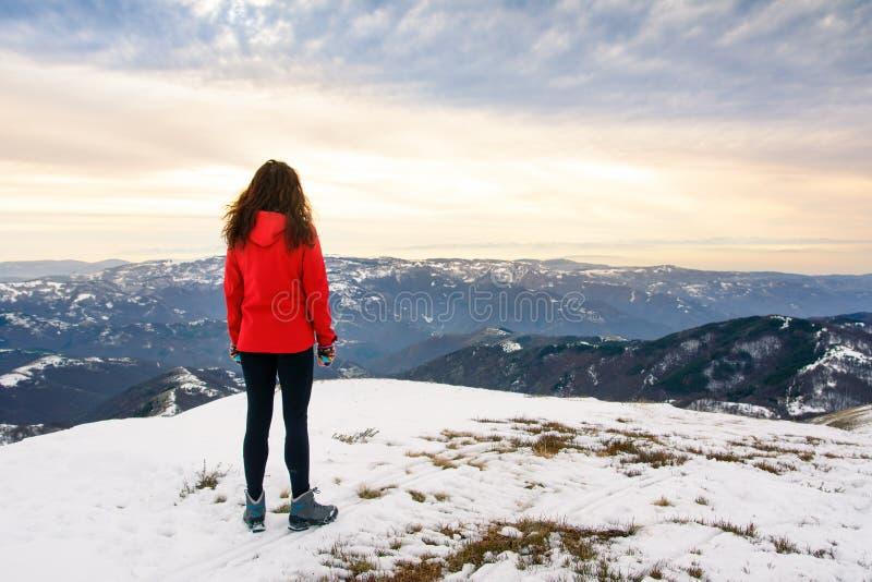 Женский hiker на снеге покрыл верхнюю часть горы стоковая фотография rf