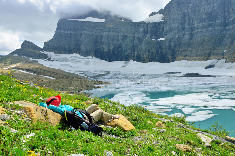 Женский hiker отдыхая ледником в много ледников, g Grinnell стоковая фотография