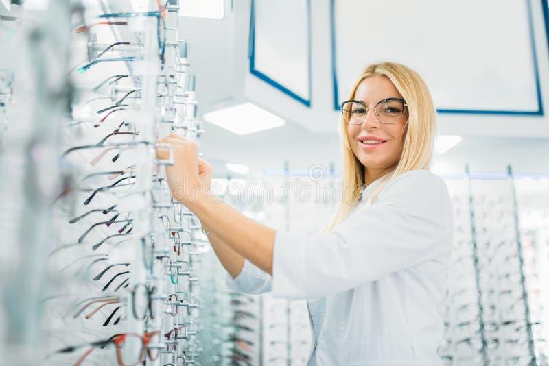 Женский optician показывает стекла в магазине оптики стоковое фото