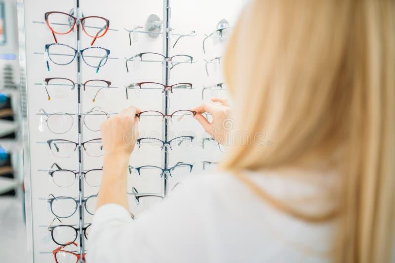Женский optometrist показывает стекла в магазине оптики стоковая фотография rf