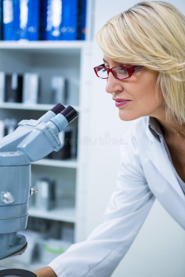 Женский optometrist смотря через микроскоп стоковые изображения rf