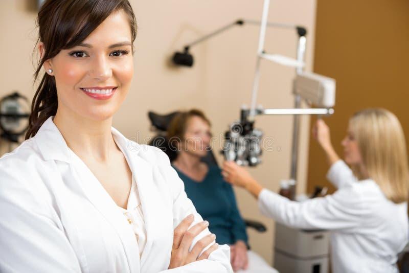 Женский Optometrist с рассматривать коллеги стоковая фотография