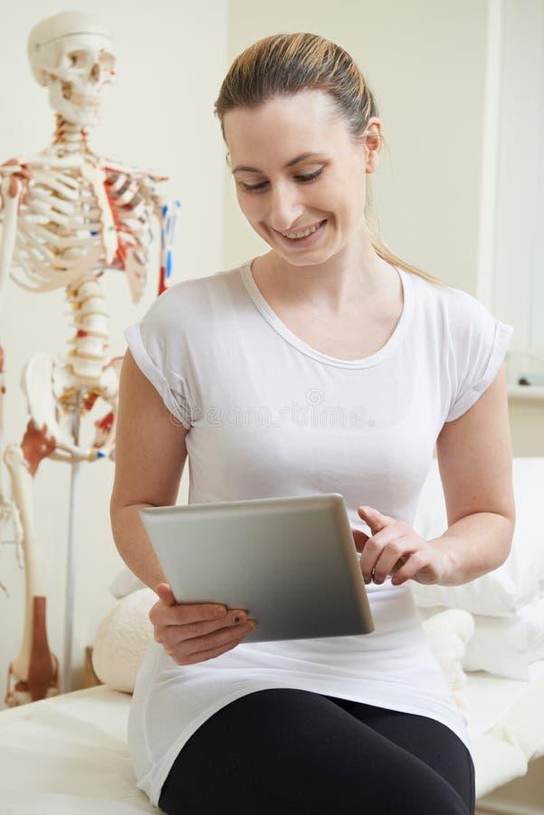 Женский Osteopath в кабинете врача используя таблетку цифров стоковые изображения rf