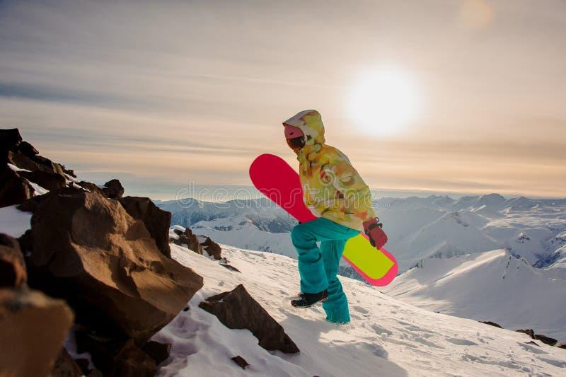 Женский snowboarder в sportswear с розовым сноубордом идя o стоковое фото rf