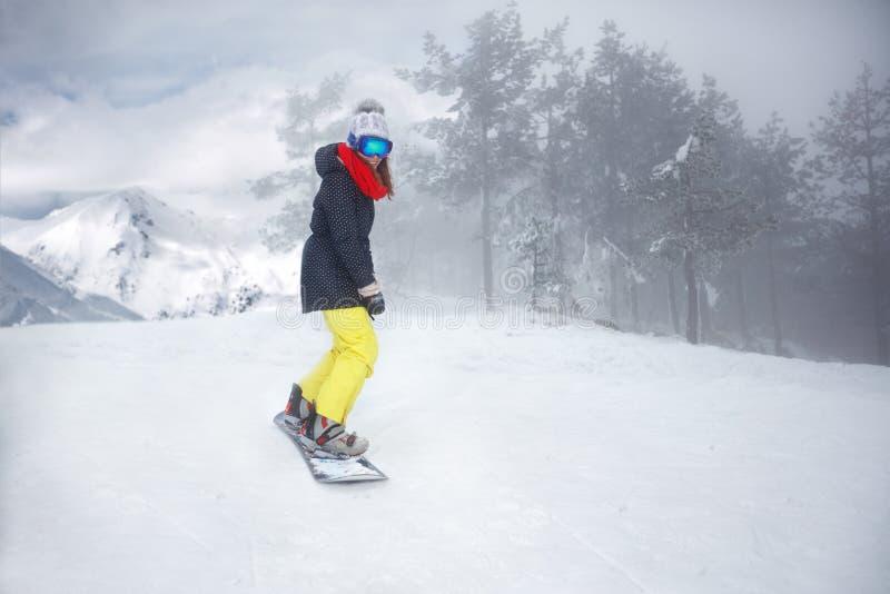Женский snowboarder на сноуборде на горе стоковые фотографии rf