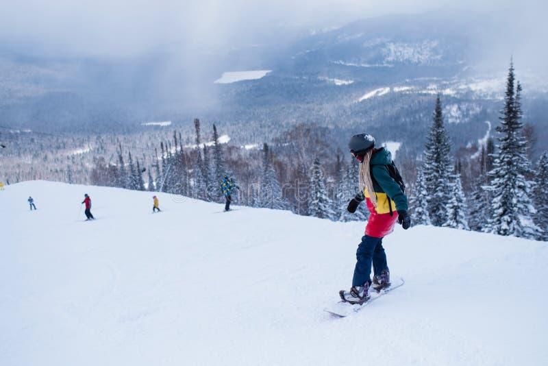 Женский snowboarder сползает вниз снежный наклон r стоковое изображение rf