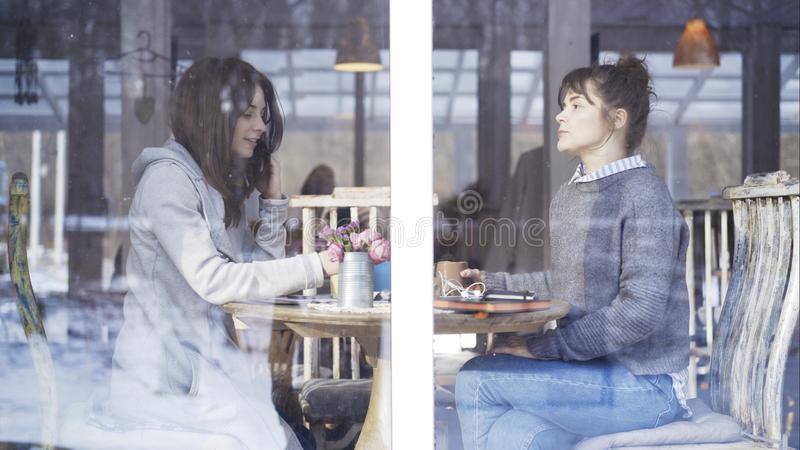 2 женских друз встречая в кафе для того чтобы поговорить стоковая фотография rf