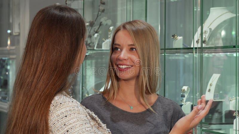 2 женских друз выбирая ювелирные изделия для покупки в магазине стоковое фото rf
