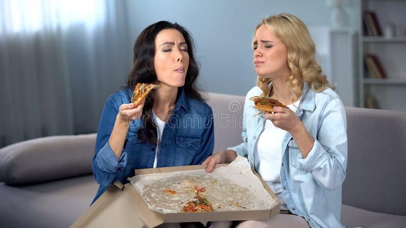 2 женских друз есть пиццу дома, выходящ последняя часть в коробку, партия девушек стоковые фото