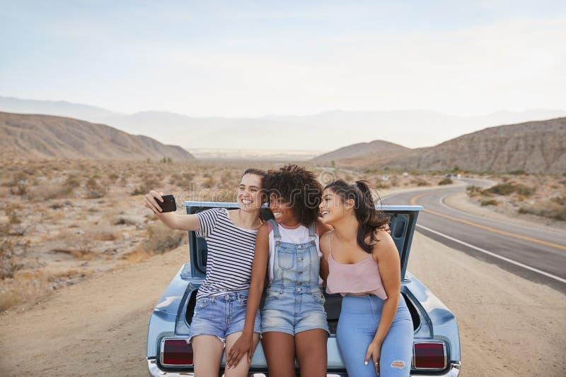 3 женских друз представляя для Selfie сидя в хоботе классического автомобиля на поездке стоковые фотографии rf