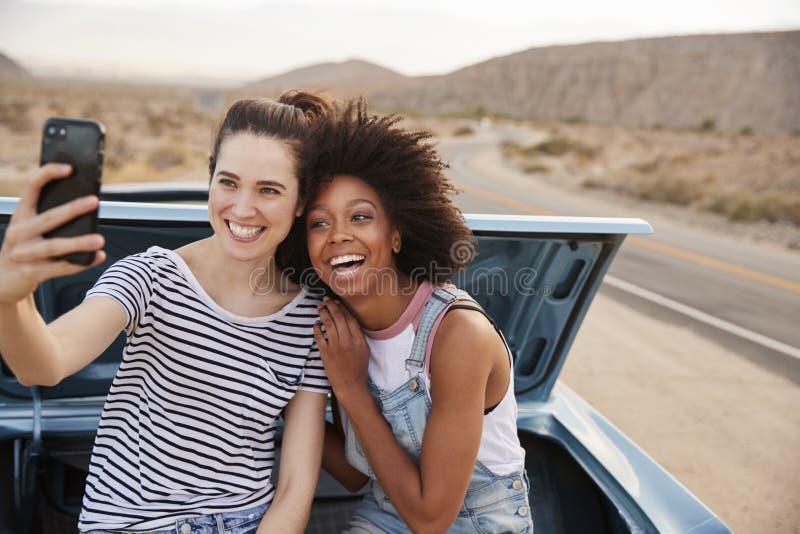 2 женских друз представляя для Selfie сидя в хоботе классического автомобиля на поездке стоковые изображения rf