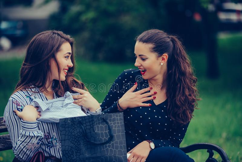 2 женских друз сидя на скамейке в парке после ходить по магазинам и делить их новые приобретения друг с другом стоковое изображение