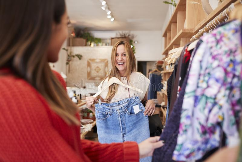 2 женских друз ходя по магазинам в независимом магазине одежды смотря шкафы стоковые фото