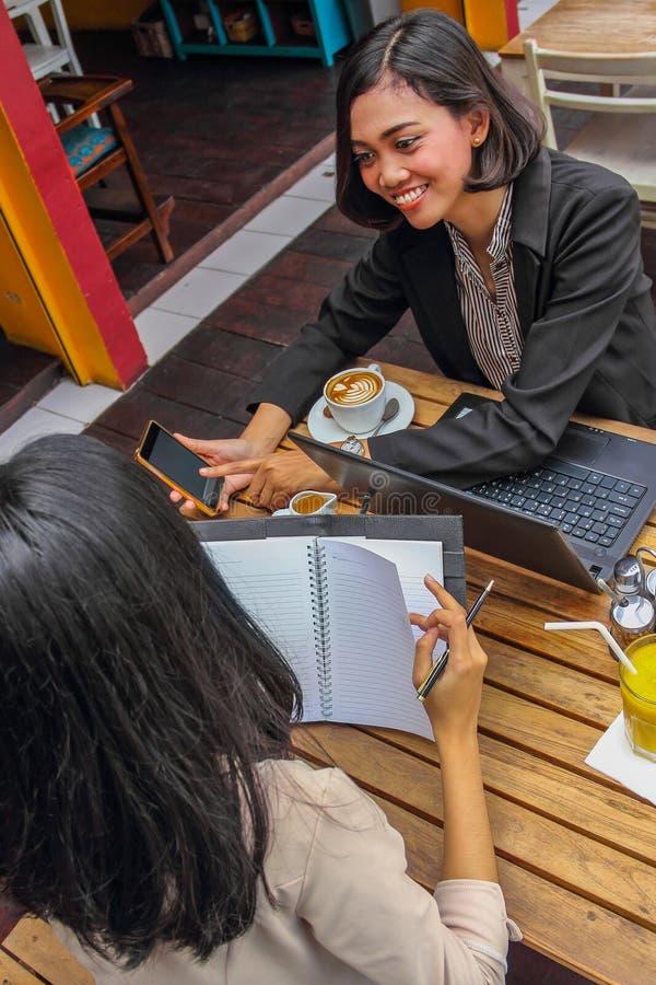 2 женских профессиональных работника имея обсуждение на кофейне стоковое фото