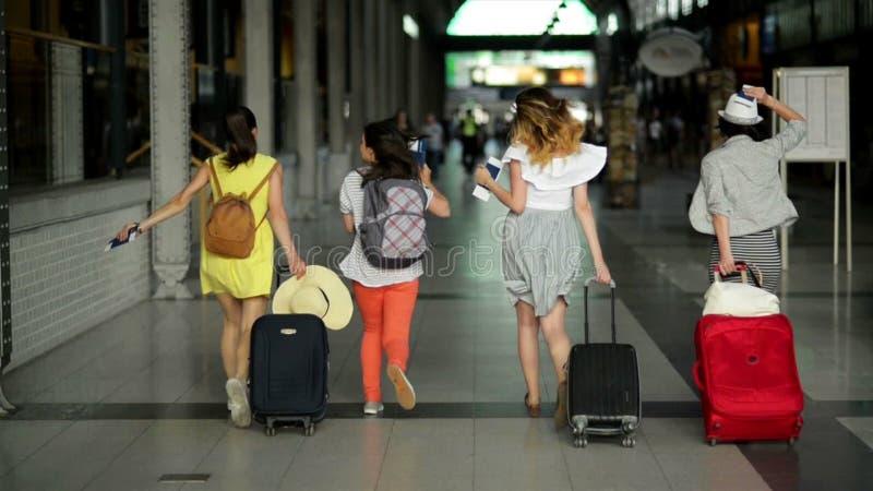 4 женских друз в яркой одежде лета последние для их самолета Красивые девушки бегут внутри авиапорта сток-видео
