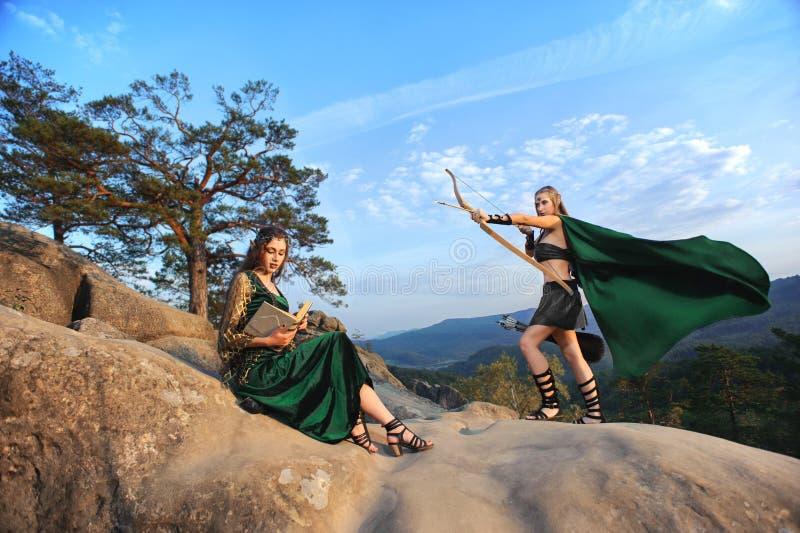 2 женских эльфа идя в древесины стоковые изображения