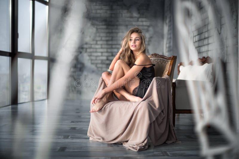 Женское бельё обольстительной сексуальной шикарной женщины нося в кресле дома стоковая фотография