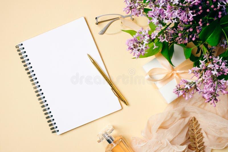 Женское место для работы с тетрадью бумаги, золотой ручкой, шарфом шелка, аксессуарами, пурпурными цветками сирени на бежевой пре стоковая фотография rf
