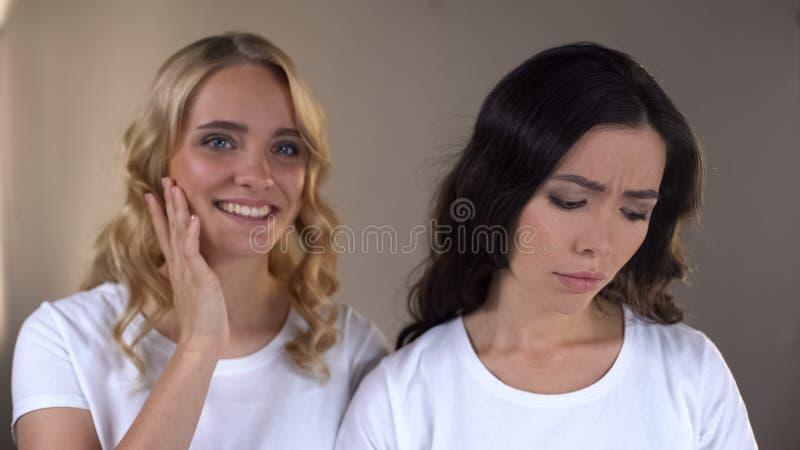 Женское наслаждаясь отражение в зеркале, расстроенный друг невзлюбит, сложный стоковое фото