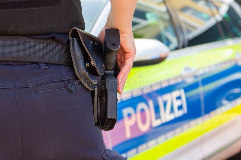 Женское полицейский держит ее руку на ее оружии Polizei немецкое слово для полиции стоковое изображение