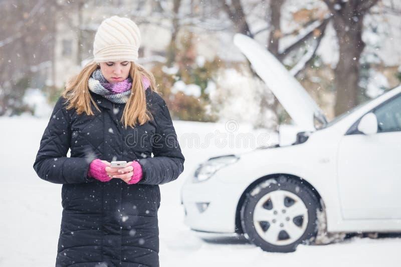 Женское положение рядом с сломленным автомобилем и использование телефона app передвижной помощи умного стоковая фотография