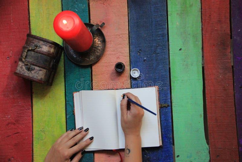 Женское сочинительство руки на тетради окруженной с аксессуарами офиса Взгляд сверху стола работы Женское сочинительство руки в д стоковое фото
