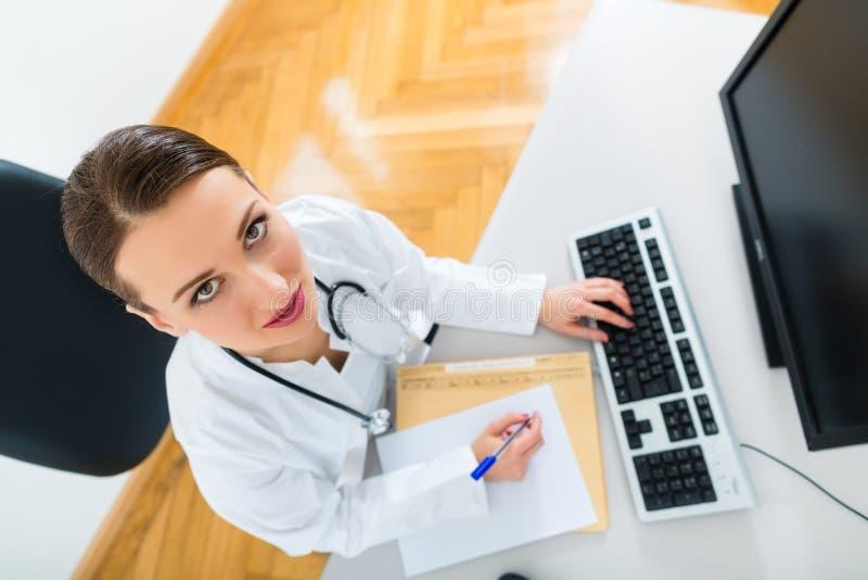 Женское сочинительство доктора в документе стоковая фотография rf