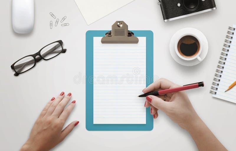 Женское сочинительство руки на тетради окруженной с аксессуарами офиса стоковая фотография rf