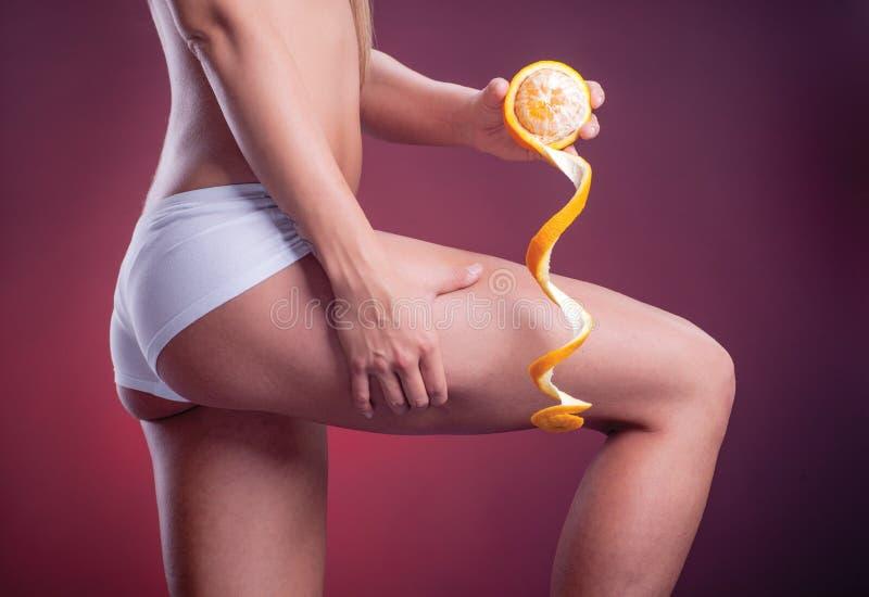 Женское тело с апельсином на фиолетовой предпосылке градиента стоковое фото rf