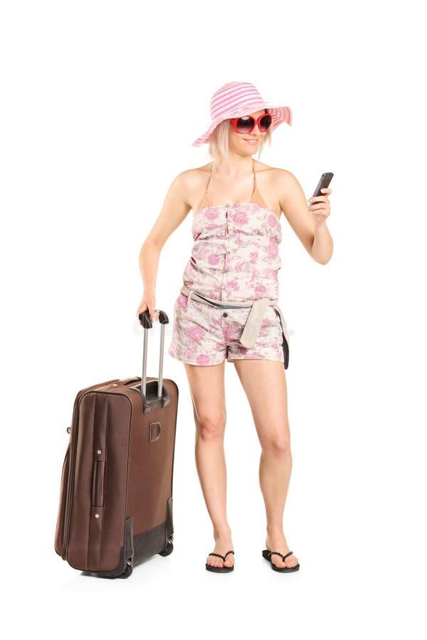 Женское туристское смотрящ ее сотовый телефон стоковые фотографии rf