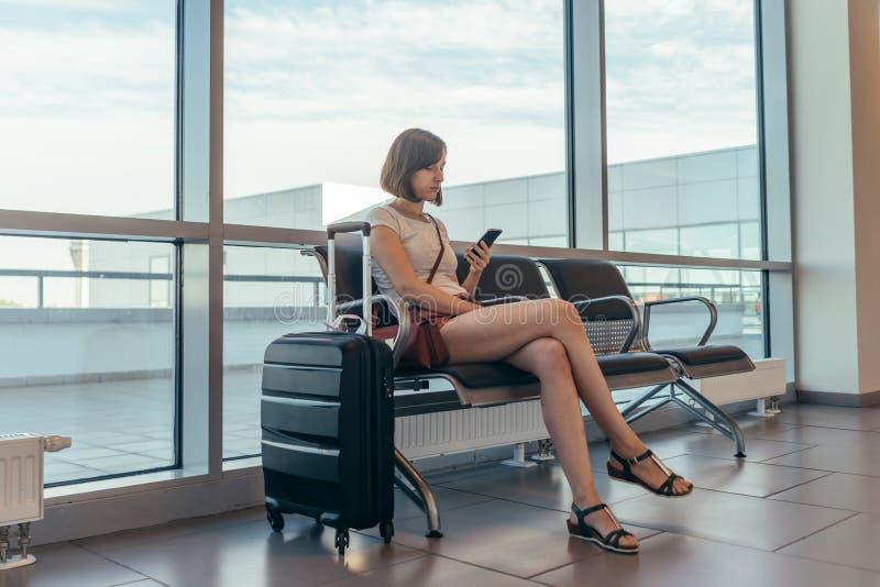 Женское туристское усаживание на стенде с багажем в зале ожидания в аэропорте стоковое изображение