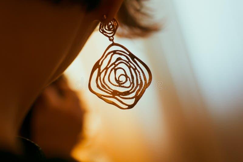 Женское ухо в серьгах ювелирных изделий стоковые фотографии rf