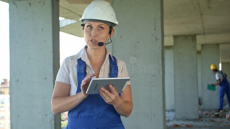 Женское чтение инженера по строительству и монтажу планирует используя цифровую таблетку и беседу к работникам через внутренние с стоковое фото rf