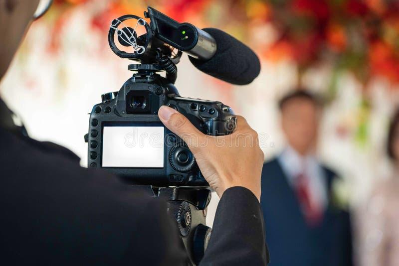 Женское Videographer в задней стороне прогоняющ и записывающ видео в событии свадьбы стоковые изображения rf