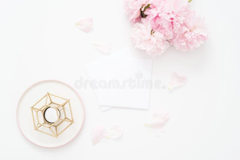 Женственная квартира свадьбы или дня рождения кладет состав с букетом и свечой пионов флористическим Карточка чистого листа бумаг стоковые фото